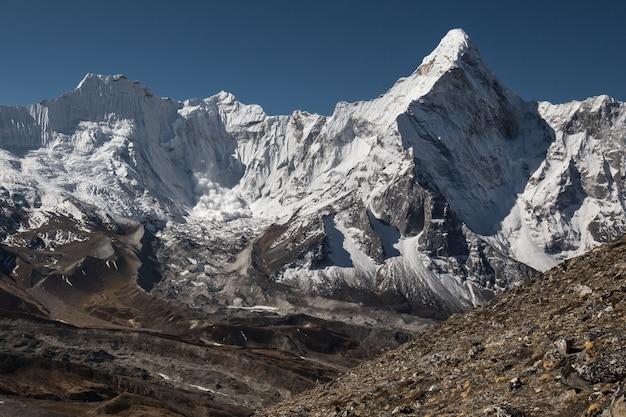 Lawina uderza w lodowiec ze zbocza góry ama dablam w himalajach