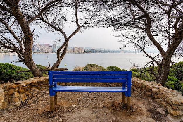 Ławka do siedzenia i kontemplacji morskiego pejzażu z miastem nad morzem. calpe alicante.
