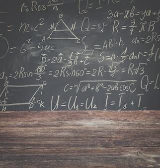Ławka szkolna z formuł matematycznych napisanych białą kredą na tle czarnej tablicy