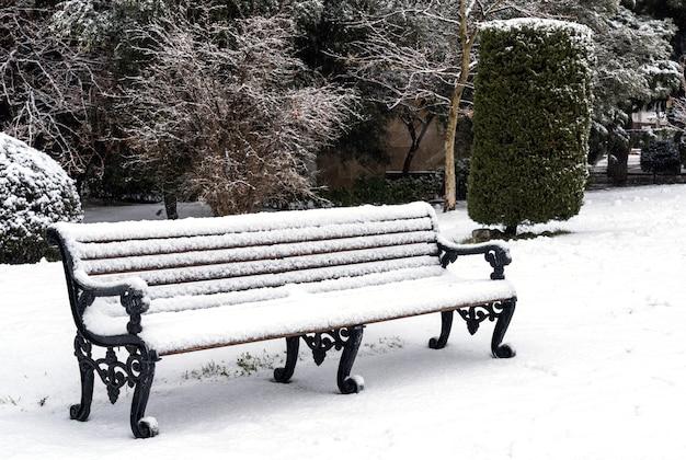 Ławka w parku miejskim pokryta śniegiem