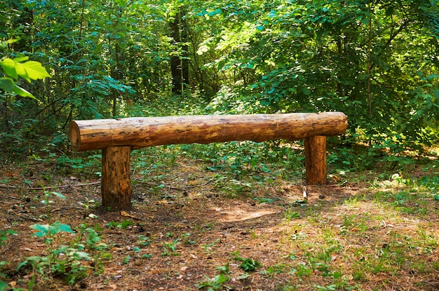 Ławka z drewnianych bali dla ludzi w zielonym lesie.