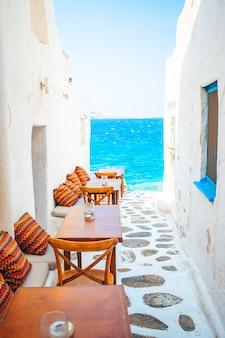 Ławki z poduszkami w typowej greckiej kawiarni na świeżym powietrzu na mykonos z niesamowitym widokiem na morze na cyklady