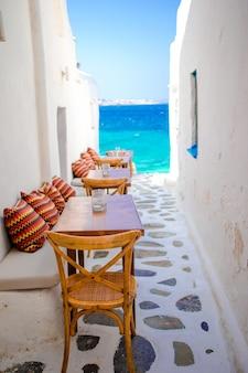 Ławki z poduszkami w typowym greckim barze na mykonos z niesamowitym widokiem na morze na cykladach