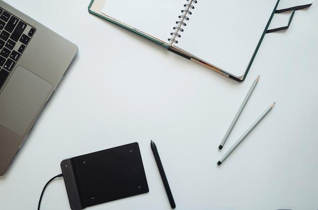 Layout dla ilustratorów, projektantów, artystów z laptopem, tabletem graficznym z rysikiem oraz notatnikiem z ołówkami. płaski, widok z góry.