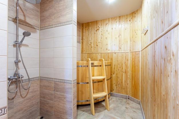 Łazienka w tradycyjnym stylu z brązowymi i beżowymi ścianami. minimalistyczny prysznic z sauną hotelową