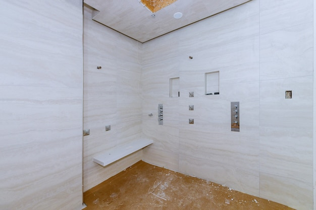 Łazienka z natryskiem wyłożona płytkami w mieszkaniu będącym w budowie, remont remontowy oraz rekonstrukcja ściany łazienki