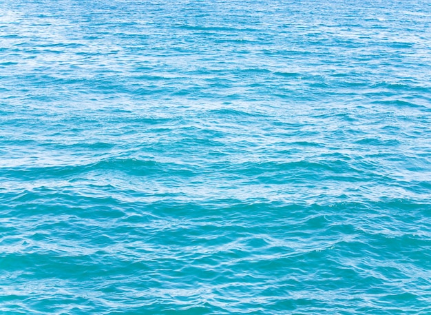 Lazurowa powierzchnia wody morskiej z odbiciami fal i chmur