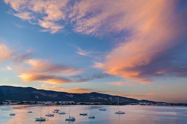Lazurowy port. lazurowy port z mnóstwem żaglowców i kutrów w całkowitym spokoju o zachodzie słońca. w oddali widać wybrzeże i góry za którymi skrywa się zachodzące słońce oświetla chmury.