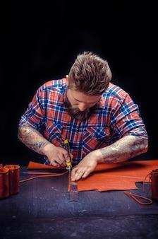 Leather artist pracuje z galanterią skórzaną w swojej garbarni