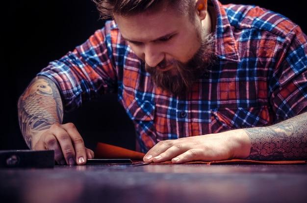 Leather artist tworzący nową produkcję skór w pracowni kaletniczej