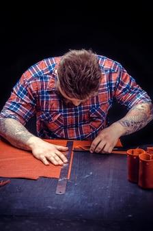 Leather currier obrabia skórzany przedmiot w swoim studio