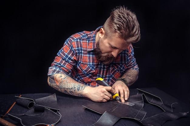 Leather currier tworzący nową produkcję skór w miejscu pracy.