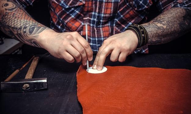 Leather skinner wycina skórzane kształty dla nowego produktu w swoim warsztacie.