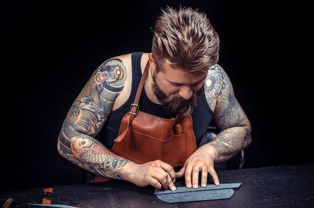 Leather tanner skupił się na swojej pracy w sklepie skórzanym