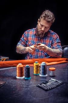 Leather tanner tworzy nowy produkt skórzany. / nożyce do skóry wycinają skórzane kontury do swojej nowej produkcji w sklepie skórzanym.