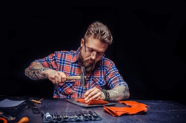 Leather tanner wycina skórzane obrysy do swojej nowej produkcji w studio.