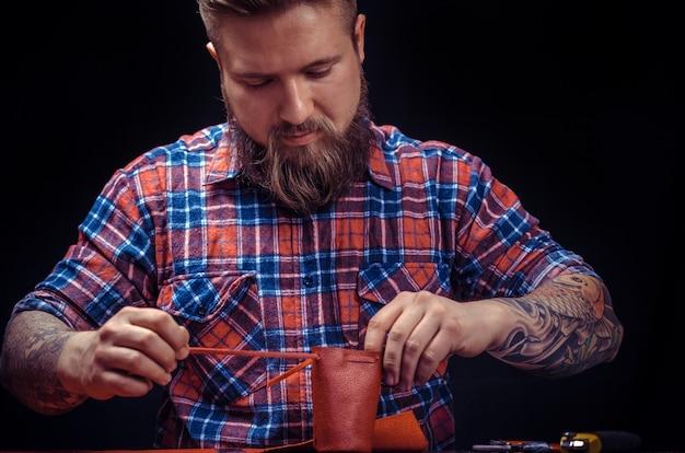 Leather worker produkuje galanterię skórzaną w sklepie ze skórą