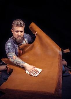 Leather workman tworzy nowy produkt skórzany w sklepie skórzanym. / leather workman zajmuje się skórą.