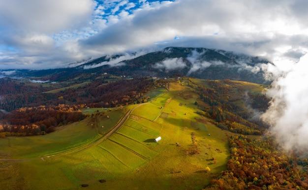 Leć nad krajobrazami zielonych wzgórz pod warstwą białych i puszystych chmur
