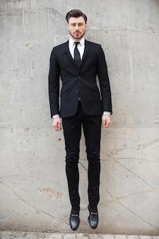 Lecąc do nowego celu. pełna długość przystojnego młodego mężczyzny w formalnej odzieży skaczącego przed betonową ścianą na zewnątrz