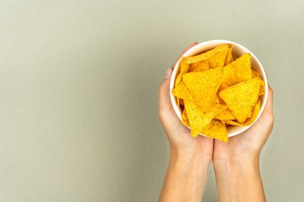 Leczenie chrupiących chipsów nachos w talerzu i kobiece dłonie na kolorowym tle.