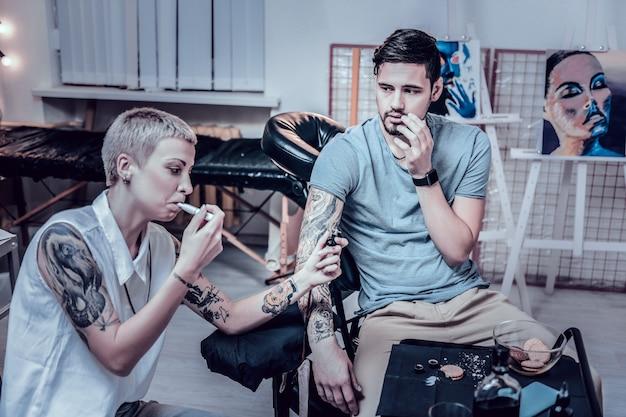 Leczenie ciasteczkami. wielofunkcyjny tatuażysta pracujący jednocześnie z tatuażem i paleniem elektronicznego papierosa