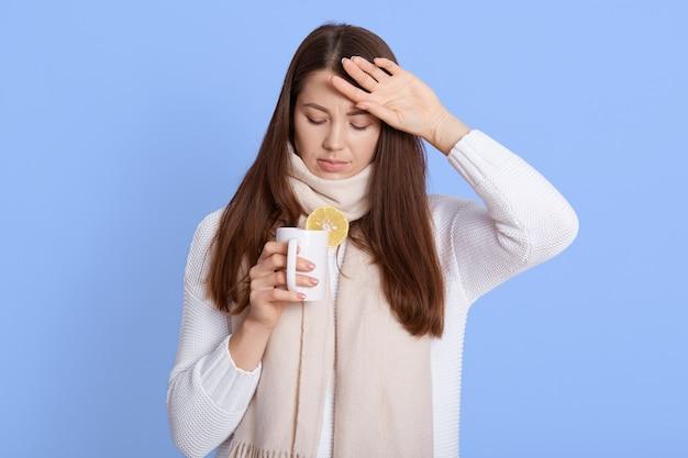 Leczenie grypy. portret chorej młodej kobiety zawiniętej w szalik, pijącej gorącą herbatę, ma sezonową grypę, infekcję wirusową, pozowanie na niebieskiej ścianie.