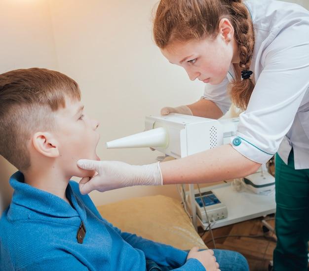 Leczenie i rozgrzewanie krtani młodego chłopca. współczesna pediatria.