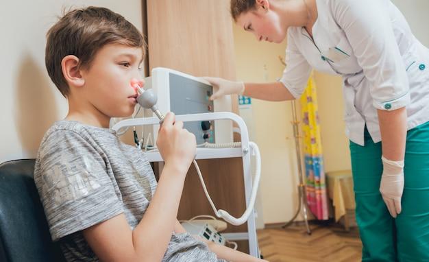 Leczenie i rozgrzewanie nosa młodego chłopca. współczesna pediatria.