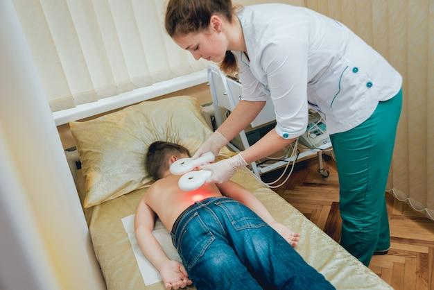 Leczenie i rozgrzewanie pleców młodego chłopca. współczesna pediatria.