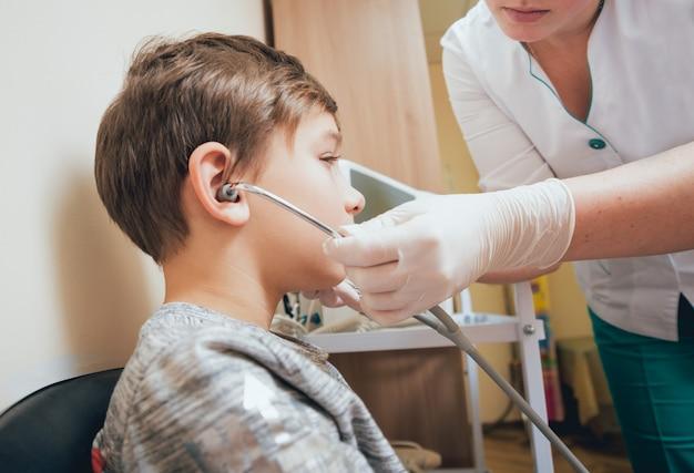 Leczenie i rozgrzewanie uszu młodego chłopca. współczesna pediatria.