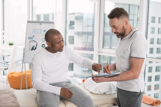Leczenie. miły miły człowiek wskazujący na notatki lekarzy, zadając mu pytanie