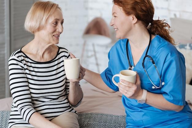 Leczenie pozytywnymi emocjami. uprzejma wdzięczna dojrzała kobieta zaprasza lekarza na herbatę po tym, jak pomogła jej w leczeniu