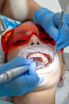 Leczenie próchnicy. dziewczyna w recepcji u dentysty