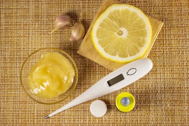 Leczenie przeziębień i grypy. różne leki, termometr, tabletki na przeziębienie, spray do gardła, krople do nosa, cytryna na brązowym tle. leczenie grypy. skopiuj miejsce.medycyna płasko świeckich.