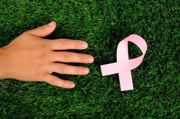 Leczenie raka, pomocna dłoń na zielonej trawie, symbol różowej wstążki.