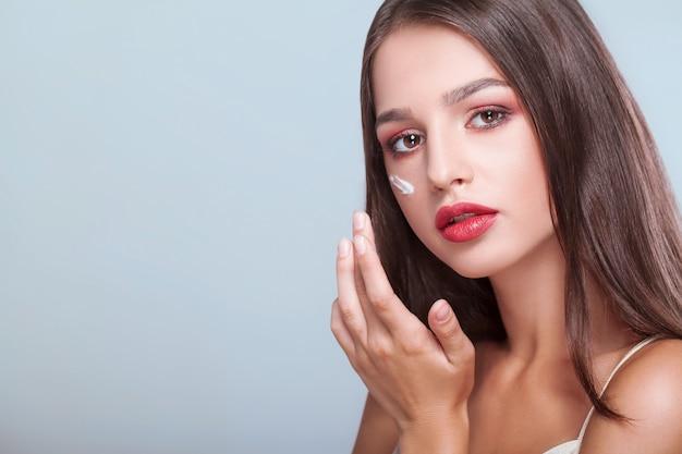 Leczenie twarzy kobieta o zdrowej twarzy stosowania kremu kosmetycznego pod oczami