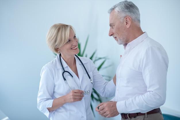 Leczenie. uśmiechnięta blondynka lekarka trzymając pigułki w blistrze