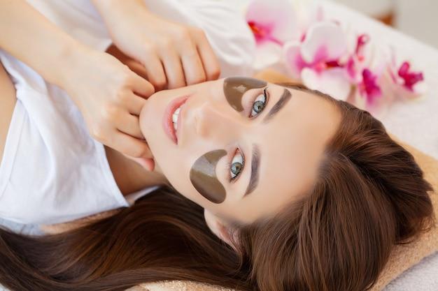 Leczenie uzdrowiskowe, piękna kobieta z opaską na twarzy w salonie kosmetycznym.