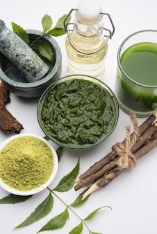 Lecznicza ajurwedyjska azadirachta indica lub liście neem w moździerzu i tłuczku z pastą neem, sokiem i gałązkami, proszkiem i olejem, selektywne skupienie