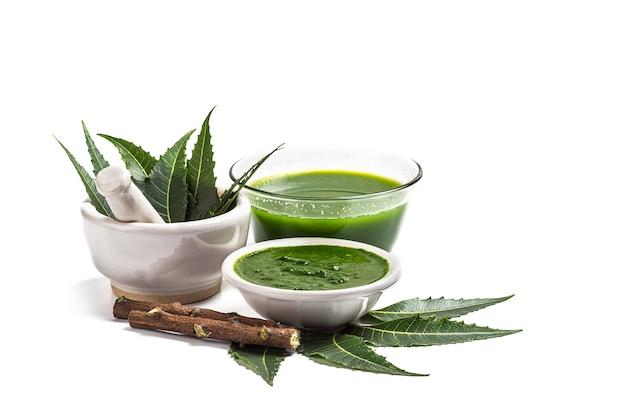 Lecznicze liście neem w moździerzu z pastą neem, sokiem i gałązkami na białej powierzchni