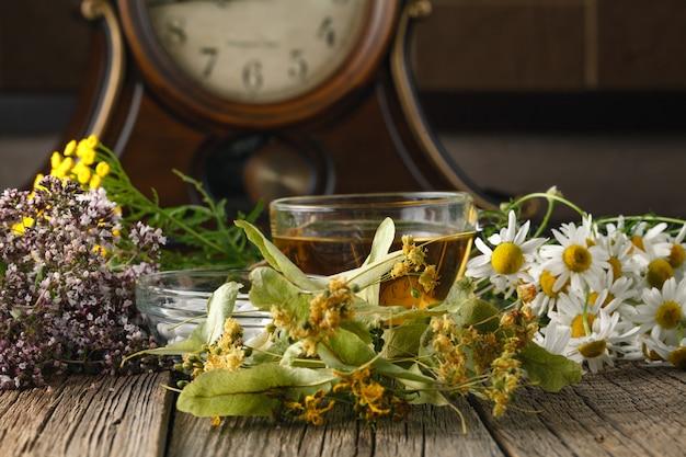 Lecznicze zioła i miska tabletek na drewnianym stole