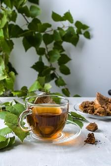 Leczniczy napar z grzybów brzozowych chaga w szklanych kubkach i kawałkach chaga.