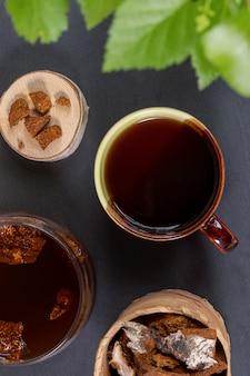 Leczniczy napój z chaga z brzozy w ceramicznym kubku i szklanym słoju, kawałki chaga na czarno. widok z góry, zdjęcie pionowe.