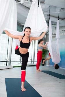 Legginsy i top. wysportowana i szczupła kobieta ubrana w czarne legginsy i top wykonująca jogę latania