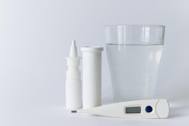 Lek w aerozolu do nosa, biała pigułka, cyfrowy termometr medyczny, szkło