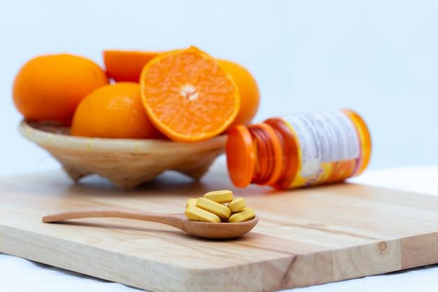 Lek w drewnianej łyżce na niewyraźnym tle plastra pomarańczy i butelki kapsułki,