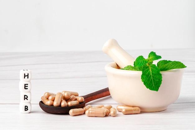 Lek ziołowy w kapsułkach z liśćmi ziół dla zdrowego życia.
