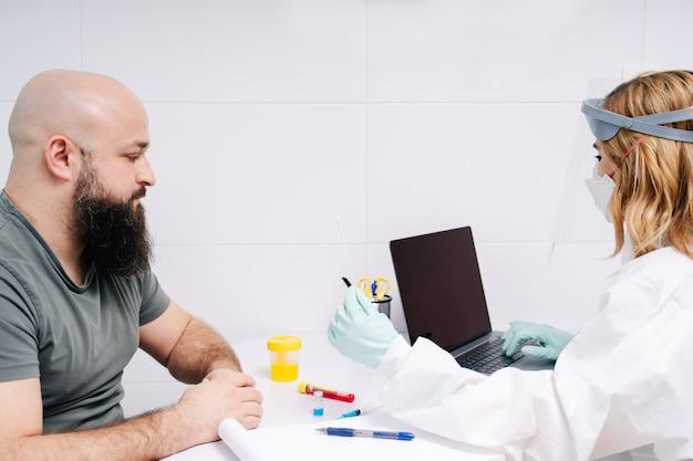 Lekarka bada pacjenta bawełnianym wacikiem w szpitalnym laboratorium