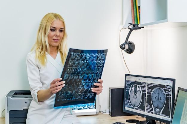 Lekarka czytająca obraz rentgenowski w pobliżu maszyny do rezonansu magnetycznego.
